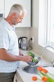Casual man rinsing broccoli in colander Royalty Free Stock Photo