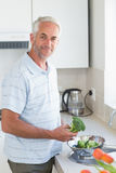 Casual man rinsing broccoli in colander and smiling at camera Stock Images