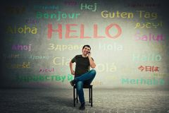 Casual man seated on a chair talking on mobile phone. Happy manager speaking different languages with his clients stock image