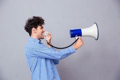 Casual man shouting on megaphone. Over gray background Stock Photography