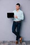 Casual man showing blank laptop screen Royalty Free Stock Photos