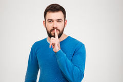 Casual man showing finger over lips Stock Photography