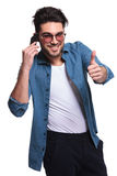 Casual man showing the thumbs up gesture Stock Images