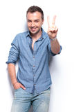 Casual man shows victory sign Stock Image