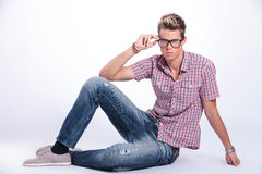 Casual man sits & adjust specs. Casual young man sitting on the floor and adjusting his eyeglasses while looking at the camera with serious expression. on Royalty Free Stock Images