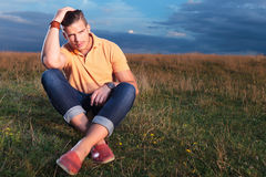 Casual man sits in grass with a hand in his hair Stock Images