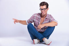 Casual man sits and points to side Stock Photos