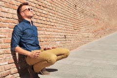 Casual man sits by wall Royalty Free Stock Photography