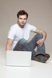 Casual man sitting behind blanck laptop Stock Image