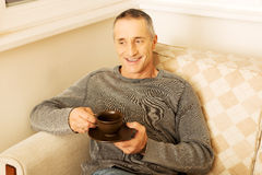 Casual man sitting on couch drinking coffee Royalty Free Stock Photo