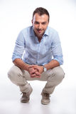 Casual man sitting crouched and smiling Royalty Free Stock Image