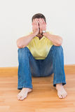 Casual man sitting on floor covering his face at home Stock Images