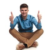 Casual man sitting on the floor  makes ok sign. On white background Royalty Free Stock Images