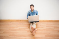 Casual man sitting on floor using laptop Stock Photography