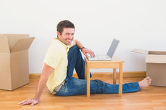 Casual man sitting on floor using laptop on the coffee table at home Stock Photos