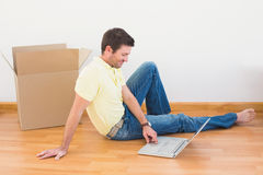 Casual man sitting on floor using laptop at home Stock Images