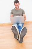Casual man sitting on floor using laptop at home Royalty Free Stock Photos