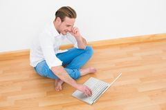 Casual man sitting on floor using laptop at home Royalty Free Stock Images