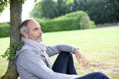 Casual man sitting in garden Stock Photo
