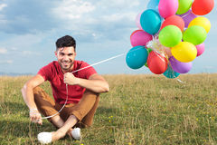Casual man sitting on the grass with balloons Royalty Free Stock Photos