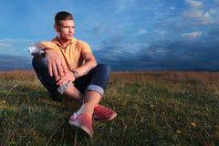 Casual man sitting on the ground and looking away Stock Photography