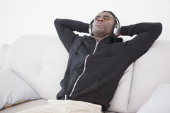Casual man sitting on his sofa listening to music Stock Image