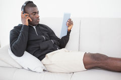 Casual man sitting on his sofa listening to music on tablet pc Stock Images