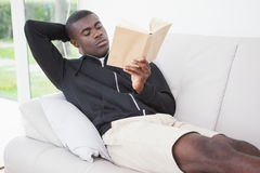 Casual man sitting on his sofa reading a book Royalty Free Stock Photo