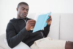 Casual man sitting on his sofa reading a book Royalty Free Stock Images
