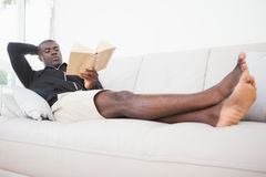 Casual man sitting on his sofa reading a book Stock Photography