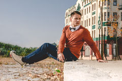 Casual man sitting on the sidewalk in  old city and looking asid Stock Image