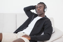 Casual man sitting on sofa enjoying music with eyes closed Royalty Free Stock Photo
