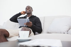 Casual man sitting on sofa enjoying music on his tablet pc Stock Photo
