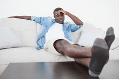 Casual man sitting on sofa with feet up Stock Photos