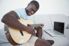 Casual man sitting on sofa playing the guitar with laptop Stock Photos