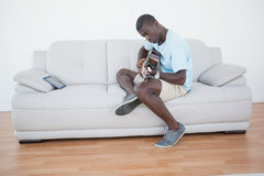 Casual man sitting on sofa playing the guitar with tablet pc. At home in the living room Stock Photo