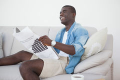 Casual man sitting on sofa reading the paper Royalty Free Stock Photo