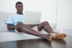 Casual man sitting on sofa using laptop with feet up Royalty Free Stock Photo