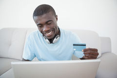 Casual man sitting on sofa using laptop to shop online Royalty Free Stock Photo