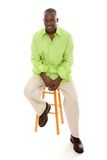 Casual Man Sitting On Stool. Casual young African American man standing in a bright green shirt sitting comfortably on a stool Stock Image