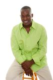 Casual Man Sitting On Stool. Casual young African American man standing in a bright green shirt sitting comfortably on a stool Stock Images