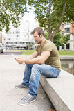 Casual man sitting in the street and holding tablet computer Stock Photos