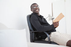 Casual man sitting on swivel chair reading a book Royalty Free Stock Image