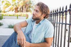 Casual man sitting and thinking Royalty Free Stock Image