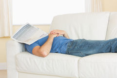 Casual man sleeping on couch with newspaper on his head Stock Photography