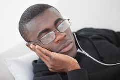 Casual man sleeping on his sofa wearing glasses Royalty Free Stock Image