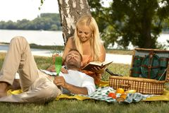 Casual man sleeping at picnic in lap of girlfriend. Casual handsome men sleeping at picnic in lap of attractive blonde girlfriend reading a book. Smiling Royalty Free Stock Photo
