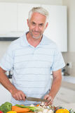 Casual man slicing vegetables and smiling at camera Royalty Free Stock Image