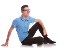 Casual man smiles while sitting on the floor Royalty Free Stock Photos