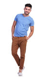 Casual man standing with hands in pockets and smiles. Full body picture of a young casual man standing with hands in pockets and smiles Royalty Free Stock Photography